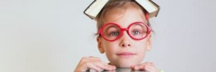 little-girl-in-red-glasses-with-a-book-on-head-lies-smiling-in-front-of-the-pile-of-books
